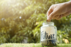 hand putting coin into jar labeled future